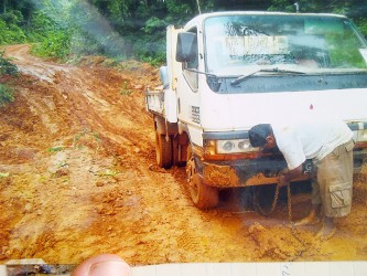 A truck driver on the deteriorated Mahdia Road preparing to have his vehicle pulled out