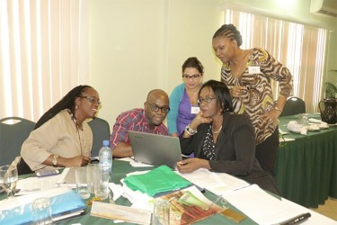 Vybzing Guyana 2014 facilitators engaged with a presentation. From left are Angela Parris, Manager of the Information Services Unit, CDB; Tyrone Hall, Development Specialist and key presenter; Sharon Lindo, Development Economist and key presenter; Valerie Isaac, Operations Officer (Environment), CDB; and Neila Bobb Prescott, Senior Technical Officer/Manager, Forest Livelihoods Programme, Caribbean Natural Resources Institute, Trinidad and Tobago.