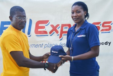 Marketing Representative of Western Union, Natheeah Mendonca hands over one of the caps to the Media XI captain Calvin Roberts.