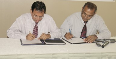 Culture Minister Frank Anthony and Radha Krishna Sharma, CEO of GT&T sign the $10 million MoU for the documentation of the National Collection. (Photo by Arian Browne)