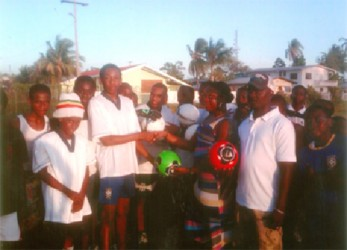 Captain of the Renaissance U17 football team Idony Jobe receives the footballs from a staff of Dynasty Sports Club and Bar.
