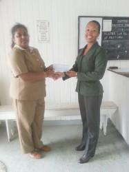 Priya Rampersaud of Sentinel Security Inc. hands over cheque to Cosmatia Lindie.