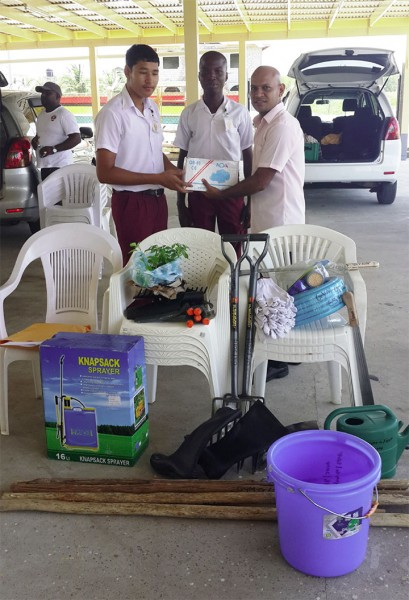 Representatives from Global Youth Movement – Guyana presenting a gift of agricultural tools to representatives from secondary schools in Region Five