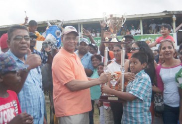 Owners of Score's Even accepts the winning trophy from Minister of Home Affairs and General Secretary of the PPP/C, Clement Rohee. (Orlando Charles photo)