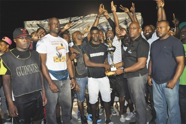 Melanie-A captain Dwight Peters collecting the championship trophy from East Coast of Demerara East Coast Branch Guinness Supervisor Clive Pellew (right) while members of the winning team, Banks DIH Limited and the Petra Organization look on