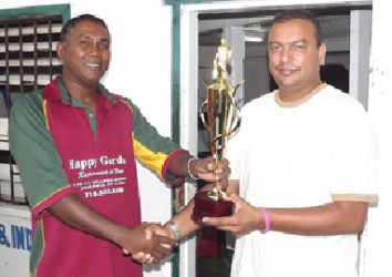 Captain of the Everest Masters Rajesh Singh (right) collects the winning trophy from Enterprise skipper Seemangal Yadram.