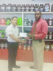 CEO of Fitness Express, Jamie McDonald hands over the sponsorship cheque to Erwyn Smith.
