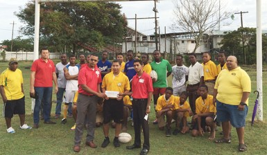 Scotiabank's representatives presenting the sponsorship cheque to one of the programme's participants, Daniel DeAbreau yesterday at the rugby field.