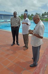 APNU MP Christopher Jones (left) inspects the pool-area with the assistance of PPP/C MP and Director of Sport Neil Kumar