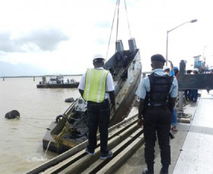 A police officer and DHB staff look on as the tug is pulled out of the river yesterday. (Photo by Aneka Edwards/Ministry of Public Works)