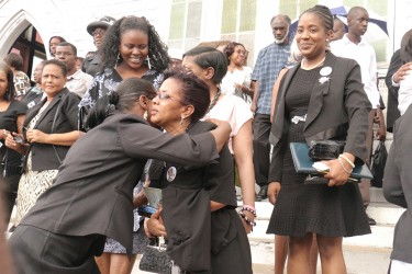 A friend comforts Lawrence Williams wife after the funeral service at the St George's Cathedral.