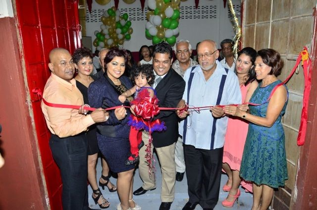 President Donald Ramotar (third from right) assists in cutting the ribbon to officially open Sueria Manufacturing Inc.  Also in photo are Joint CEOs of the company, Teshawna Lall (second from left) and Frank Sanichara, baby Sueria (centre), First Lady Deolatchmee Ramotar (right) and Kaieteur News' Publisher Glenn Lall (left) (GINA photo)