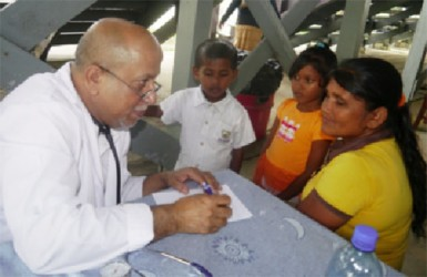 Dr. Mujahid Ghazi treating a mother and her two children