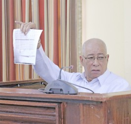 Former GDF Chief of Staff, Major-General (Rtd) Norman McLean holding up a document during his testimony yesterday. (Arian Browne photo)