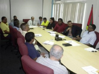 Minister of Natural Resources and the Environment Robert Persaud (second from right in background) and others at the meeting. (Ministry of Natural Resources photo)