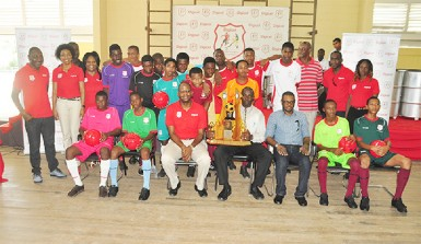 CEO of Digicel, Gregory Dean, sitting third from left, Head Master for the CWSS, Cleveland Thomas (sitting with trophy) and Regional Chairman, Sharma Solomon, third right sitting, take a photo with students of CWSS following the launch of the event yesterday. (Orlando Charles photo)