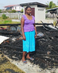 Seeta Persaud standing amid the remains of her house