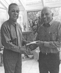 Leader of the Blairmont Crematorium project Nowrang Persaud, (left) receives the first two cheques from Trevor Subryan
