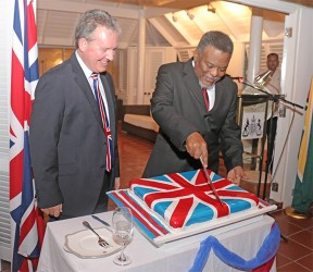 Prime Minister Sam Hinds cutting the cake at the reception last night in honour of the birthday of Queen Elizabeth II. At left is British High Commissioner Andrew Ayre. (Arian Browne photo)