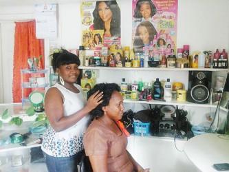 Jennifer Holder fixes a  client's hair