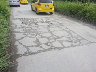 A roughly patched portion of the road.