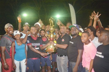 West Front Road captain Hubert Pedro (black vest) collecting the championship trophy from Mackeson Brand Manager Jamal Douglas while members of the team and spectators look on.