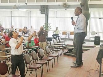 Student Glenfield Denison faces off with Vice-Chancellor Jacob Opadeyi (right) during the consultation yesterday