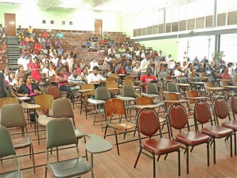 Students listen to Vice-Chancellor Jacob Opadeyi and other presenters during the consultation. Not many students were in attendance initially but the number grew as more and more trickled into the George Walcott Lecture Theatre at the Turkeyen Campus yesterday