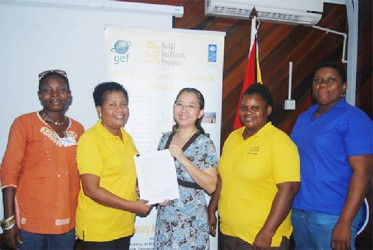 UNDP Resident Representative (ag), Ms. Chisa Mikami (centre) and Chairperson of the Kuru Kururu Farmers Crops and Livestock Association (KKFCLA), Denise Thomas (second from left) at the signing of the grant with the UNDP/GEF Small Grants Programme. Also in photograph are some of the executive members of KKFCLA.
