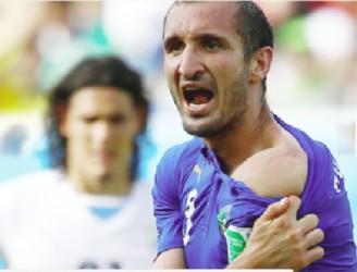 Italy's Giorgio Chiellini shows his shoulder, claiming he was bitten by Uruguay's Luis Suarez, June 24, 2014. Suarez and Chiellini clashed in a challenge in the Italian penalty area 10 minutes from the end of the match, and the furious Italian pulled open his shirt to show the mark to the referee. REUTERS/Tony Gentile