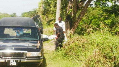 Undertakers from the Lykens Funeral Home removing the unidentified body yesterday at Le Repentir Cemetery.
