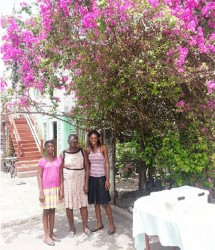 Claudette Lewis and her granddaughters Careann (left)  and Tawana (right) under their bougainvillea bush