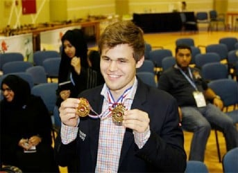 World chess champion Magnus Carlsen smiles as he displays the two gold medals certifying him the new World Rapid and Blitz Champion. The two championships were held in Dubai recently. Carlsen is now the undisputed triple crown champion of chess, having won the conventional title in November 2013 when he defeated Vishy Anand in India.
