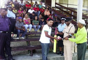 Assistant Superintendent, Joshua Harvey-John hands over some of the cricket gear to Naipaul Molaha in the presence of other officers and group members