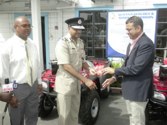 A symbolic handing over by Minister of Natural Resources Robert Persaud (right) to Commissioner of Police, Seelall Persaud. Also in photo is Commissioner of the GGMC, Rickford Vieira. (Ministry of Natural Resources photo)