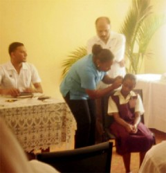 Minister of Health Dr Bheri Ramsaran (standing) looks on as a nurse fits a child with a hearing aid.