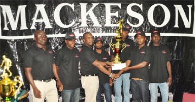 Mackeson brand manager Jamal Douglas presents West Front Road skipper Hubert Pedro with the championship trophy while tournament coordinator Kevin Adonis (far left) and team members look on.