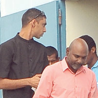 School teacher Ramesh Angatiah, right, as he appeared in the Rio Claro Magistrates' Court yesterday on two charges of indecent assault against a 16-year-old boy.