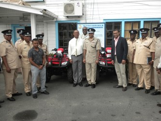 The Minister, the police and others pose with some of the ATVs (Ministry of Natural Resources photo)