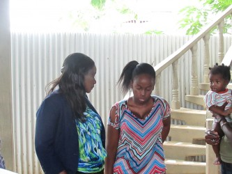 Minister of Human Services and Social Security, Jennifer Webster (left), speaking to the Bagot sisters' sibling Malkia Bagot. (Ministry of Human Services photo)