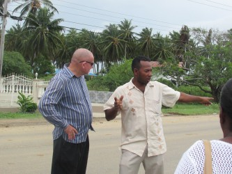 The dead sisters' brother recounts the tragedy to the Deputy Permanent Secretary Patrick Findlay (left) at the scene.  (Ministry of Human Services photo)