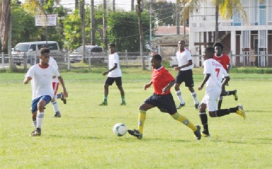 Action between Carmel Secondary (red) and Queen's College at the Eve Leary ground in their Georgetown Conference match-up