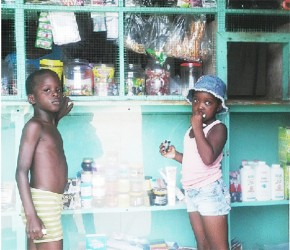 Six-year-old Stanton and four-year-old Renita waiting to buy snacks  at a Belfield shop