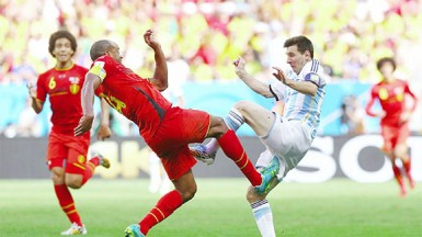 Belgium's Vincent Kompany fights for the ball with Argentina's Lionel Messi. (Reuters/Damir Sagolj)