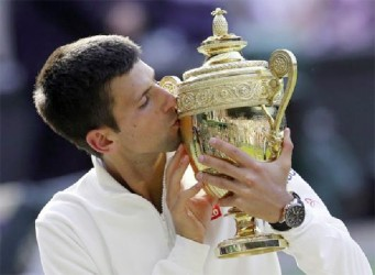Novak Djokovic of Serbia kisses the winner's trophy after defeating Roger Federer of Switzerland in their men's singles final tennis match at the Wimbledon Tennis (Championships, in London yesterday. (REUTERS/Suzanne Plunkett)