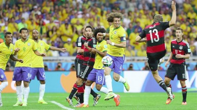 Thomas Mueller (2nd R) of Germany scores his team's first goal during the 2014 FIFA World Cup Brazil Semi Final match between Brazil and Germany yesterday. (FIFA.com photo)