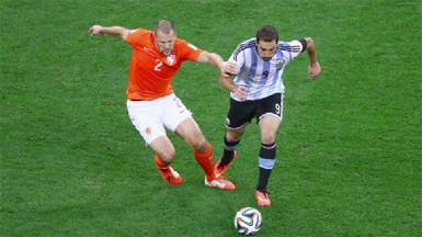 Ron Vlaar (left) of the Netherlands challenges Gonzalo Higuain of Argentina during the 2014 FIFA World Cup Brazil Semi Final match between the Netherlands and Argentina at Arena de Sao Paulo yesterday. (FIFA.com photo)