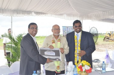 Director of Sun and Sand Hotels Bhushan Chandna (left), President Donald Ramotar (centre) and Tourism Minister Irfaan Ali holding up the hotel plan at the sod turning ceremony yesterday.