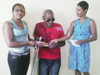Clive Richmond (centre) receiving his Bible from Indra Kowlessar left and Anjuli Beharry right.