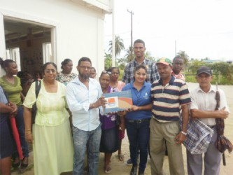 Supervisor of the OLPF Essequibo Branch Indrawattie Natram (fourth, right) hands over a laptop as residents and staff look on.